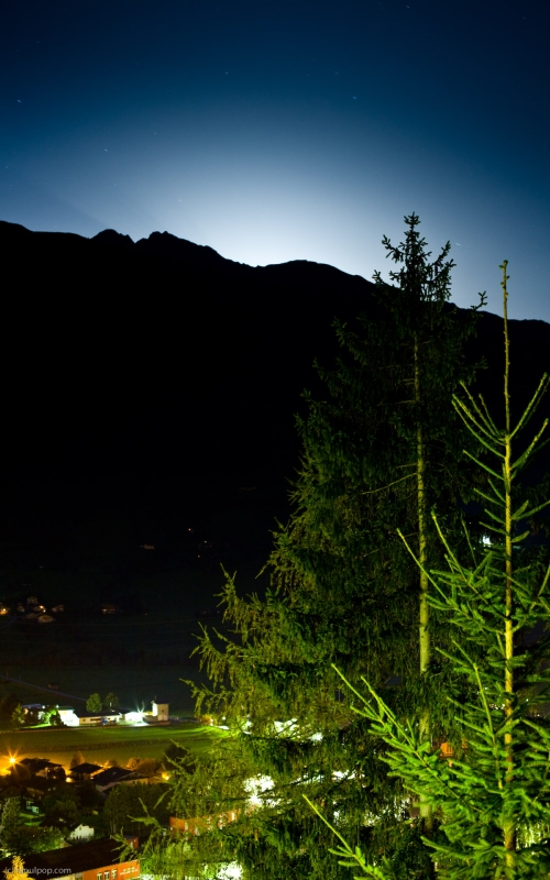 A night photograph of the village of Matrei, taken from Hotel Goldried. Various lights in the valley below illuminate the houses and fields, while moonlight casts a white glow behind the mountain in the background.