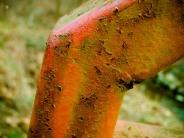 Rusty iron railing with peeling paint. Cabin John Park, Potomac, MD, USA.