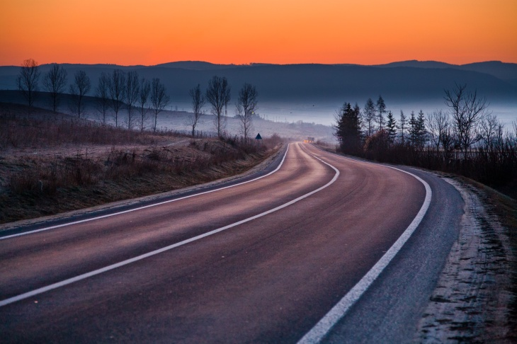 A bright orange sky above distant mountain peaks signals a new day, while a winding road descends slowly into the fog-covered valley below.