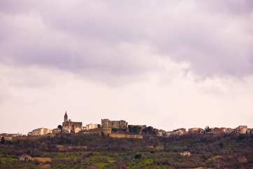 An ancient castle and town, nestled on a tall hillside in the mountainous Abruzzo region of Italy.