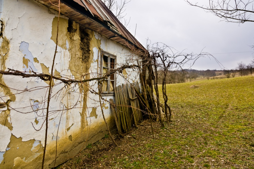 A crumbling old country house sits unused at the bottom of a hill in a little village in Moldova, Romania.