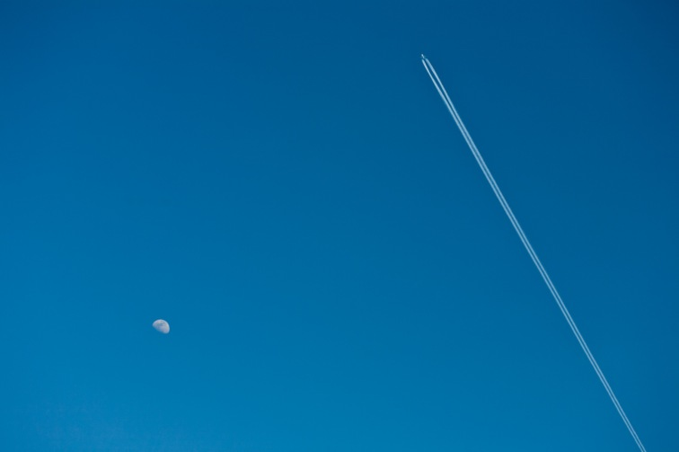 A jet airplane shoots past the moon in plain daylight.