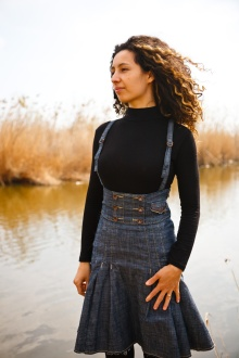 Ligia stands by a lake, dressed in a black blouse and jeans skirt.