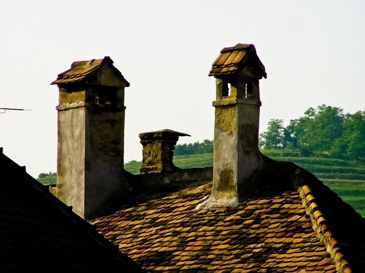 Old brick chimneys on the roof of one of the old houses in the historic city center, Medias, Romania.