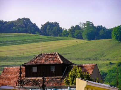 A distant hillside visible from inside the historic city center in Medias, Romania. The rooftop of one of the old German houses is visible in the foreground.