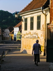 A man walks down a street in the historic city center, Medias, Romania.