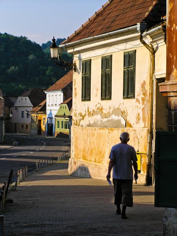 A man walks down a street in the historic city center, Medias, Romania.