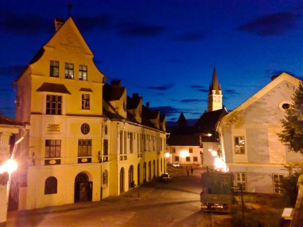 Walking in the city of Medias, Romania, on a clear summer evening. The city's main clock tower is visible above the rooflines of the buildings in the foreground.