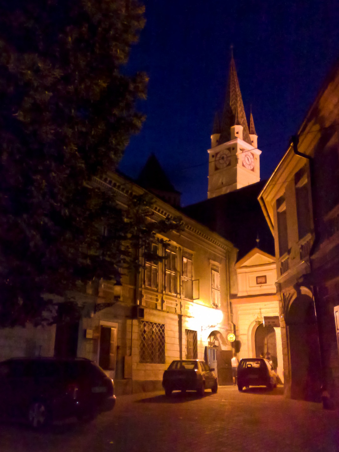 Walking in the city of Medias, Romania, on a clear summer night. The city's main clock tower is visible above the rooflines of the buildings in the foreground.