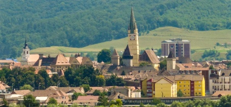 A cityscape of the city of Medias, Romania, showing the older, medieval buildings of the city. The clocktower is indeed leaning.