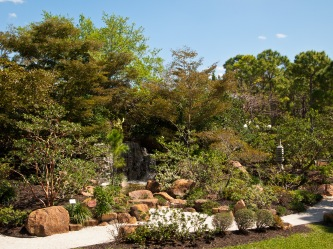 Waterfall hidden among trees, Morikami Museum and Japanese Gardens, Delray Beach, FL, USA.