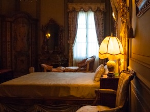 An elegant bedroom, lamp glowing softly on the nighstand. Vizcaya, Miami, Florida, USA