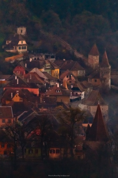 A view of some of the historic homes in the city of Sighisoara, inside the fortified walls, during twilight, as the fog began to set in.